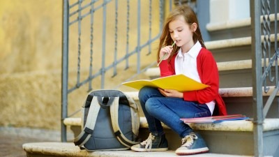 Adorable little schoolgirl studying outdoors on bright autumn day. Young student doing her homework. Education for small kids. Back to school concept.