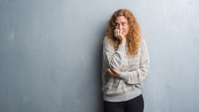 Young redhead woman over grey grunge wall looking stressed and nervous with hands on mouth biting nails. Anxiety problem.