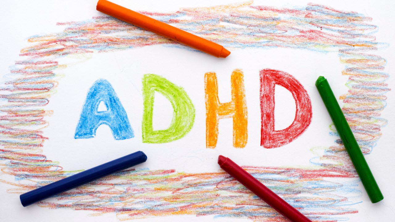 ADHD written on sheet of paper by crayons.
