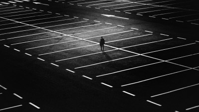 A black and white photo of a man alone in a parking lot to represent the isolation that comes with living with ADHD