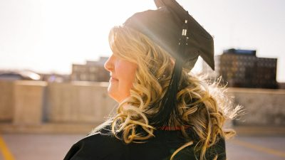 Woman in graduation regalia to demonstrate academic accomplishment