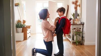 A mother getting her son ready for school.