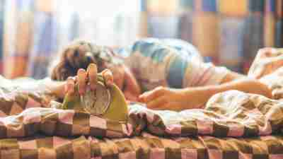 A person laying in bed sleeping with their hand over an alarm clock to show problems getting up in the morning.