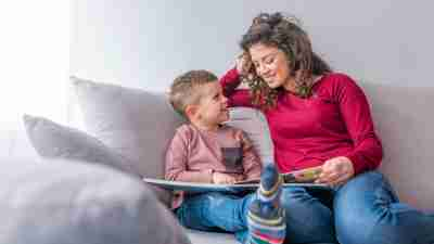 A mother reading with her son on the couch. Parents can find ADHD books for kids especially helpful in explaining the condition to young ones.