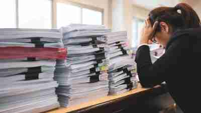 How to Organize Paperwork - A woman sitting on a desk with a pile of papers