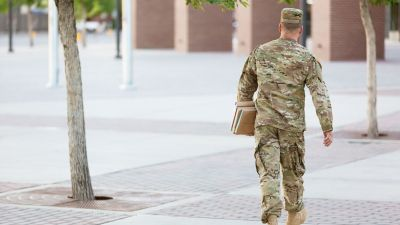 A soldier in uniform carrying books for class. An ADHD Buddy system can be helpful for adults with the condition heading to college.