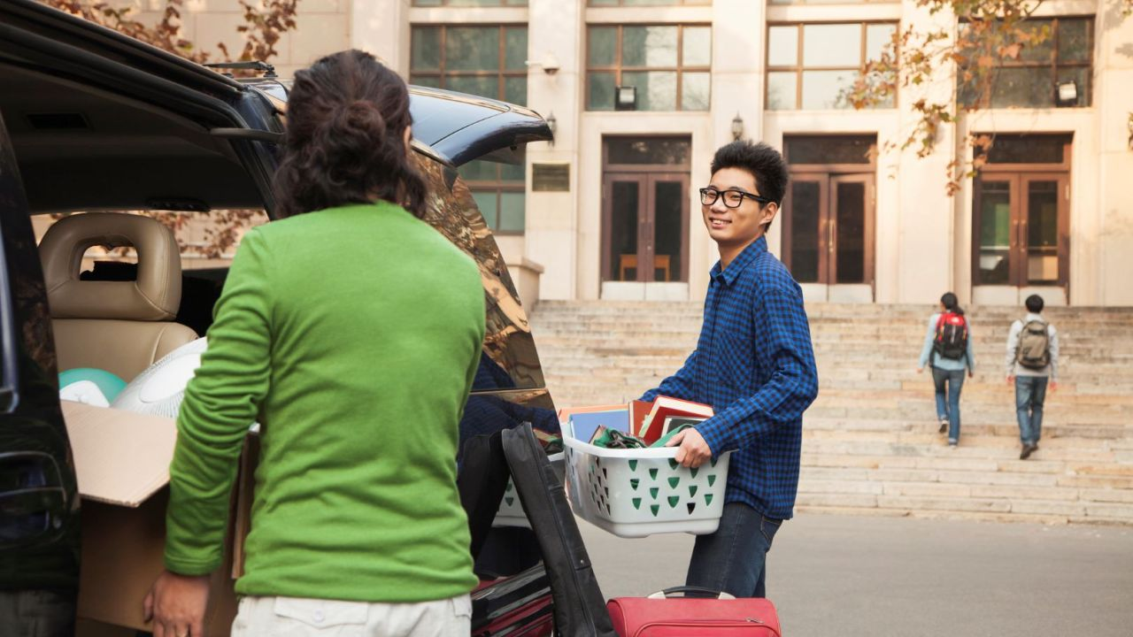 A young man moving into his college dorm with the help of his parents