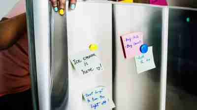 A woman opening her refrigerator door, which has several reminder sticky notes on it.