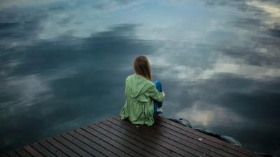 Neurodivergent woman sitting on a dock