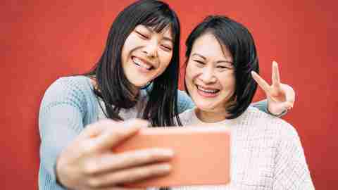 Asian mother and daughter taking photo selfie with mobile smartphone outdoor - Happy Chinese family having fun with new trends technology apps - Family, tech and lifestyle people concept