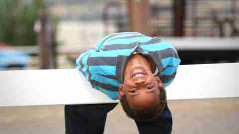 Young boy hanging upside down on fence while smiling.