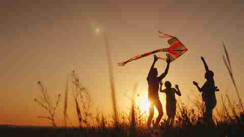 Happy family playing with a kite at sunset. Mom, Dad and daughter are happy together.