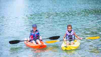 Two boys kayaking on a lake as part of a summer camp activity