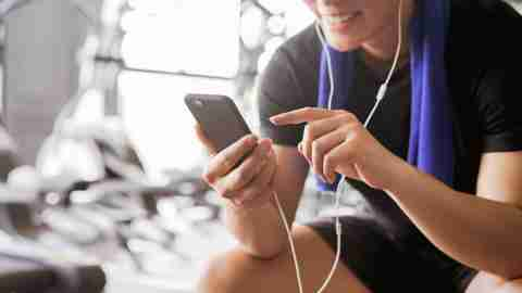 close up young asian man holding smartphone and choose list of music player for listening after finish exercise at gym, healthy lifestyle concept
