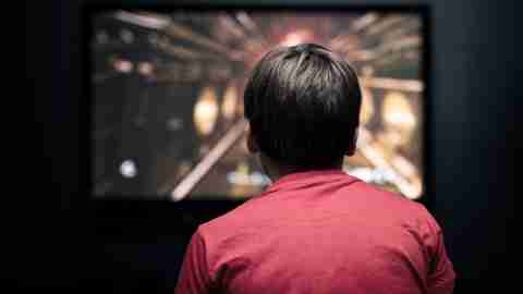 Facing back caucasian little boy playing video game on television. Television and video game addiction.