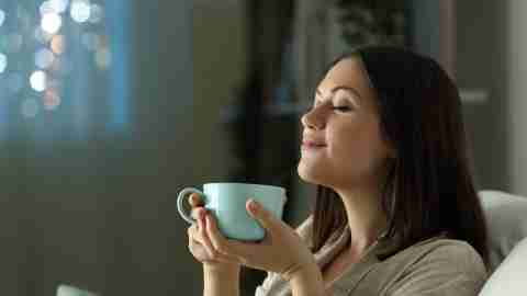A woman relaxing with tea and practicing mindfulness.