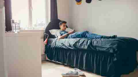 Teen boy alone in his room, isolated.