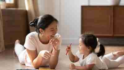 Educational pastime develop creativity skill in kid concept. Asian mother her small daughter lying on warm wooden floor in sunny cozy living room, mom teach girl paint use album and colourful pencils