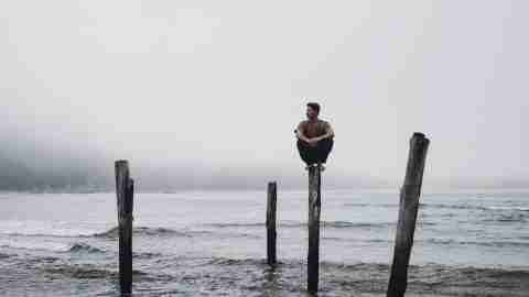 Boy with ADHD perched on dock post