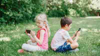 Boy and girl play games on smartphones outdoor. Kids digital gadget screen addiction. Children friends playing online sitting on grass in park. Contemporary problem of loneliness together.