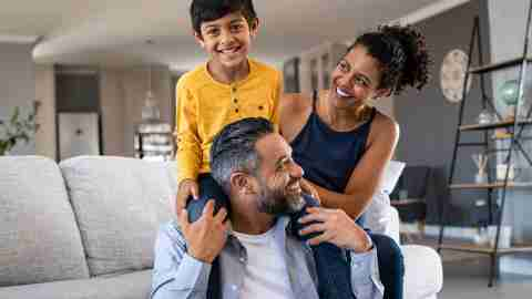 Family sitting in living room, dad carrying child over shoulders
