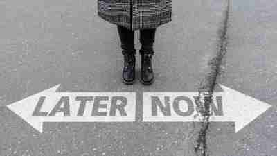 legs of woman standing behind arrow road marking with text NOW and LATER, call to action and procrastination concept