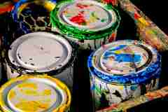 Paint pots on a black background in a messy tray