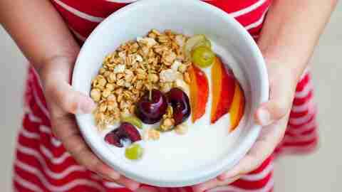 Healthy adhd breakfast. Fresh granola, muesli with yogurt, fruits and berries in little girl's hands