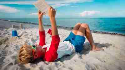 Boy reading a book at the beach