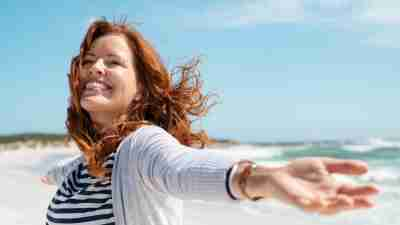 Happy mature woman with arms outstretched feeling the breeze at beach. Beautiful middle aged woman with red hair and arms up dancing on beach in summer during holiday. Mid lady in casual feeling good and enjoying freedom with open hands at sea, copy space.