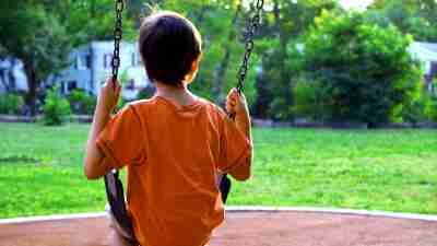 A young child, boy, sits on a playground swing alone in a park and looks off into the distance into the sunset. Rear view from behind. Sunlight outlines the head and hair. Park is empty. Boy is alone. Green grass and trees visible.