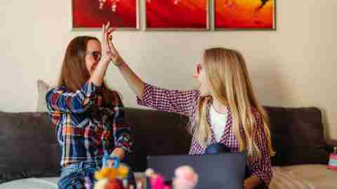 Mother helping daughter with homework, they giving high five after assignment successfully done