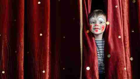 Young Boy may have autism, anxiety, adhd Wearing Clown Make Up Peering Out Through Opening in Red Stage Curtains