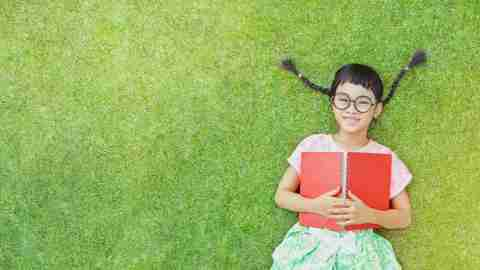 Little girl with adhd lay on grass and reading a book in a summer day