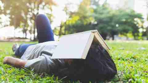 asian teenage girls are sleeping after reading a book on the grass in the park