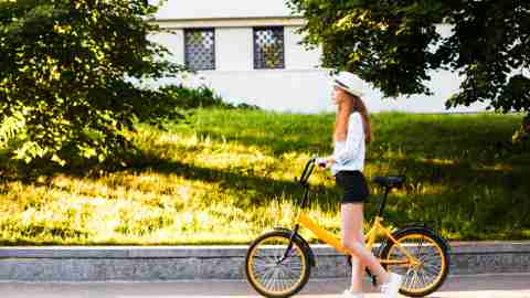 Girl teenager in a hat with a yellow bike walks through the summer city. Traveling around the city by bike.