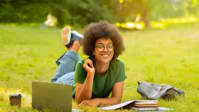 Black Student Girl Studying Outdoors With Laptop And Workbooks, Lying On Lawn At Campus And Smiling At Camera