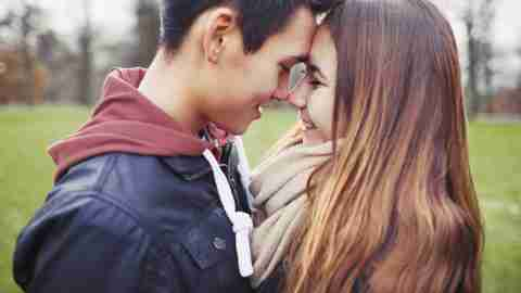 Close up of cute teenage couple in love sharing a special moment. Romantic young man and woman outdoors in park.