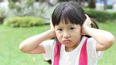 little girl with auditory processing disorder covering her ears and expressing Negativity