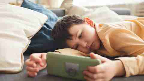 Warm-toned portrait of bored teenage boy using smartphone while lying on bed or couch at home, copy space