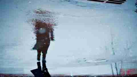 Why am I so weird? Concept image of a woman reflected through a puddle on a dark, rainy day