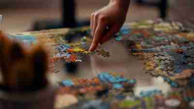 A closeup of a person's hand as they drag small puzzle pieces across a table. Photo by Ross Sneddon.