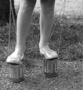 Photo from Google Images. A length of thin rope attached to the same cans would turn them into a pair of stilts.
