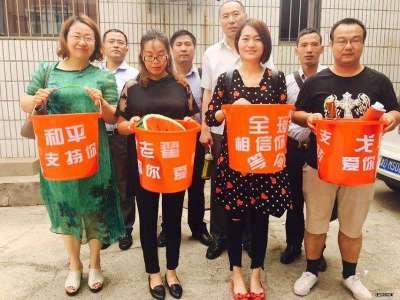 """李文足(前排右二)创意以""""红桶""""声援被抓捕的维权律师。(推特图片)"""