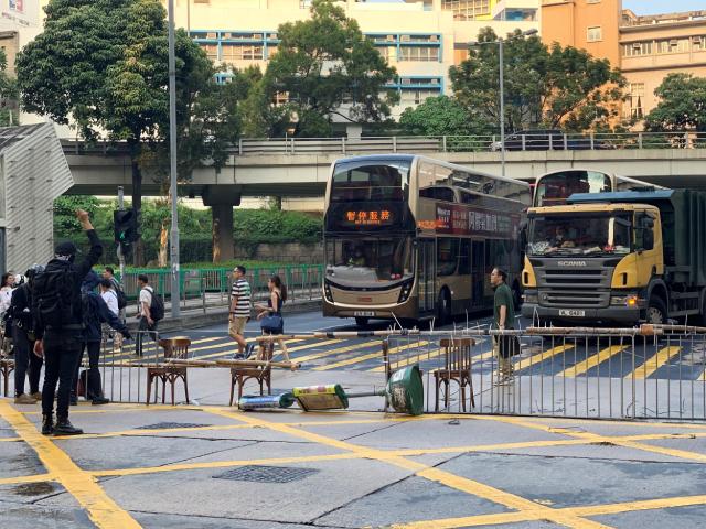 """参与""""反紧急法""""游行的示威者12日在九龙弥敦道上设置路障,公众交通受阻。"""