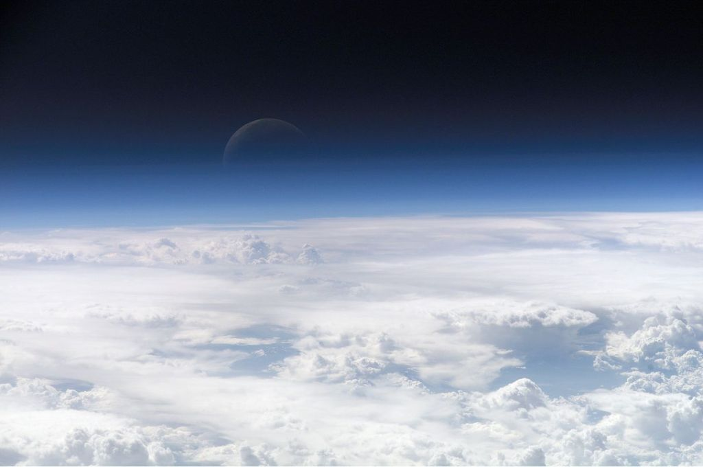 View of the crescent moon through the top of the earth's atmosphere, as seen from the International Space Station.