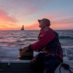 November, 2014. Leg 2 onboard Team SCA. Annie Lush trims as Team SCA and Team Alvimedica race into the sunset.