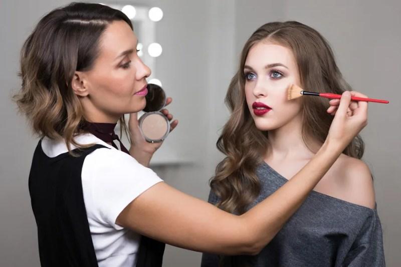 makeup artist doing model's face
