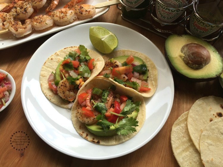 Grilled Shrimp Tacos garnished with avocado, pico de gallo and lime juice