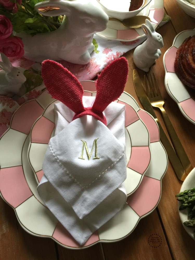 Easter brunch setup includes bunny ears and pink china